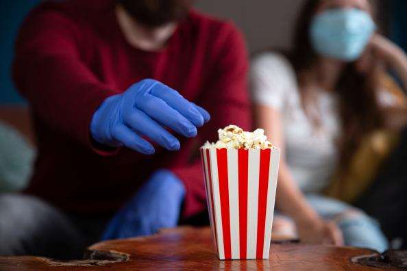 A doctor eats popcorn with a glove as he watches some movies for doctors